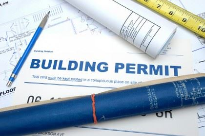 Building Permits laying on table with tape measurer and pencil