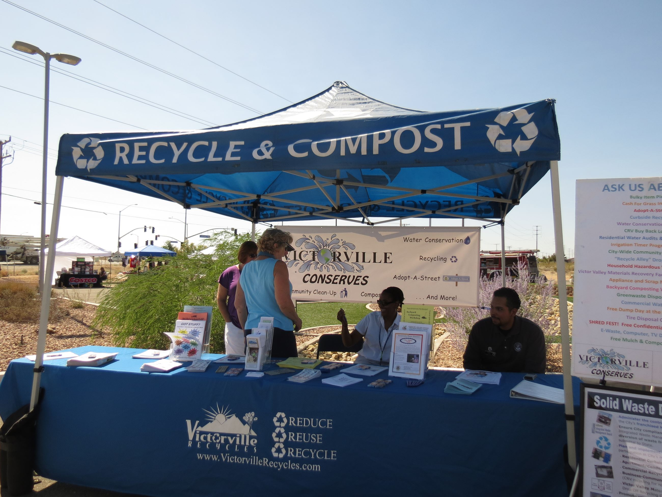 People standing under tent that says Recycle and Compost