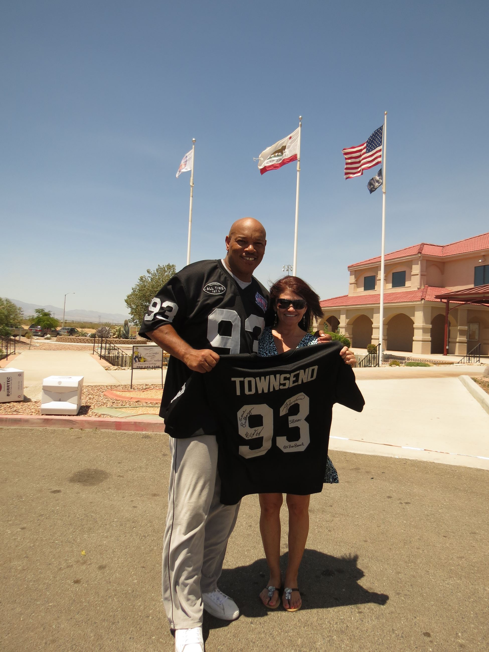 "Man in a Football jersey standing with woman both holding a jersey that says ""Townsend 93"""