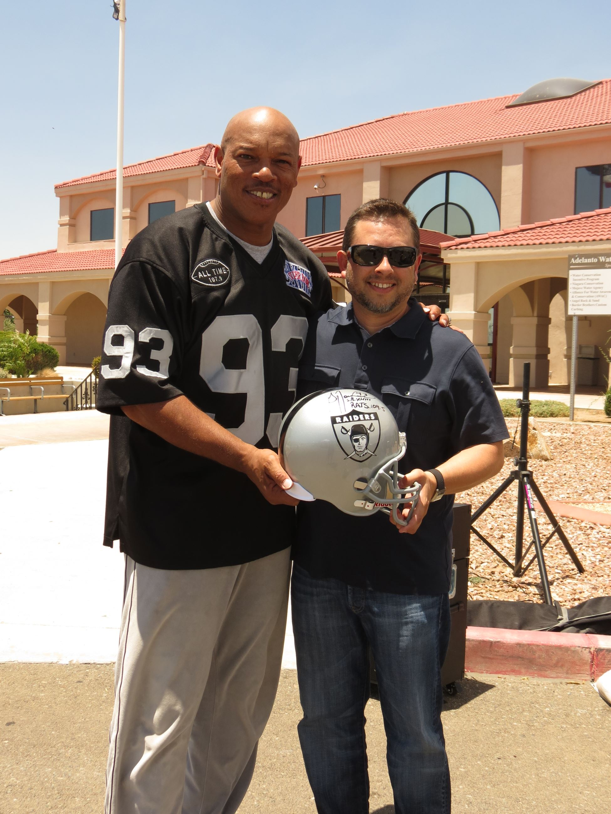 Two men holding a Raiders Football helmet